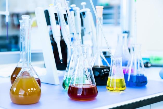 Flessen met gekleurde vloeibare reagentia in een wetenschappelijk laboratorium