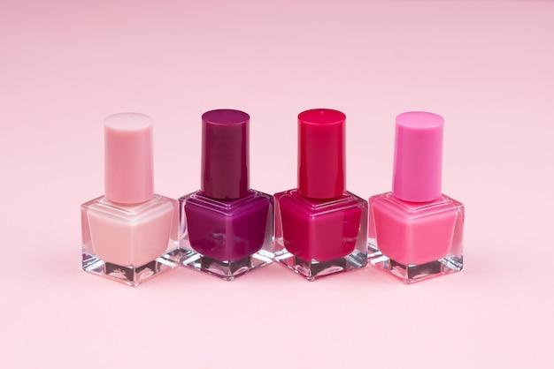 Flessen met nagellak over roze muur