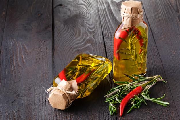 Flessen met olie, kruiden en specerijen op houten tafel op zwart