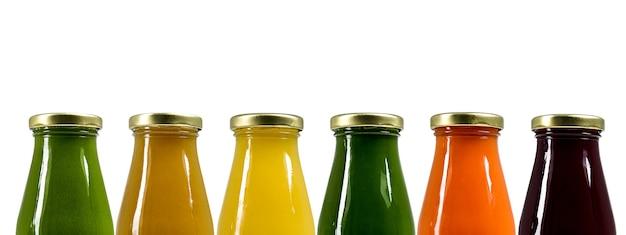 Flessen met sappen van verschillende kleuren. geïsoleerde achtergrond. gezonde levensstijl. natuurlijke vitamines.