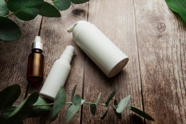 Flessen met serum en potten cosmetische crèmes op een grijze achtergrond met eucalyptustakjes en groene bladeren cosmetische producten op houten achtergrond