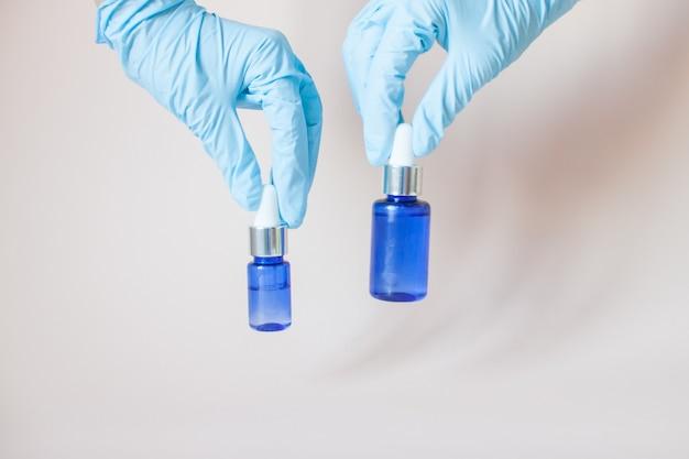 Flessen met serum voor het gezicht in zijn handen in beschermende medische rubberen handschoenen op grijs