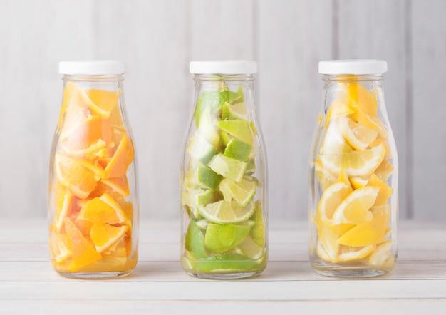 Flessen met sinaasappels met limoenen en plakjes citroenen