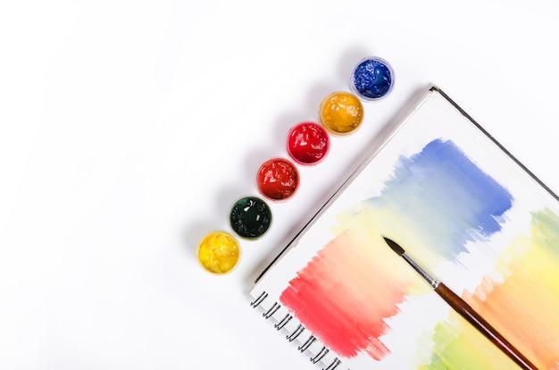 Flessen met verf en penseel met gekleurde kladblok