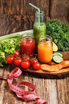 Flessen met verse groentesappen op houten tafel