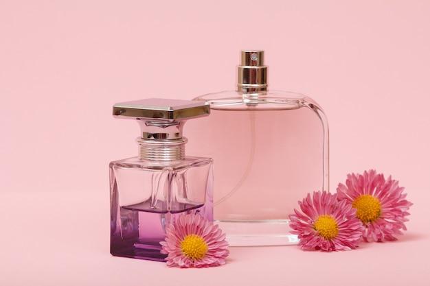 Flessen met vrouwenparfums en toppen van bloemen op een roze achtergrond. vrouwen producten.