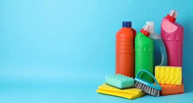 Flessen met wasmiddel en schoonmaakproducten op blauw, ruimte voor tekst