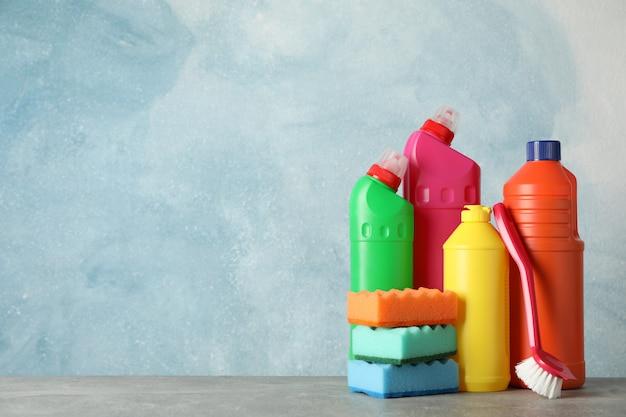 Flessen met wasmiddel en schoonmaakproducten op blauwe achtergrond, ruimte voor tekst