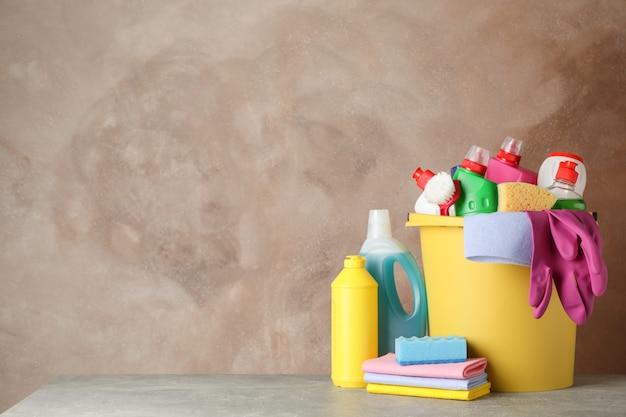 Flessen met wasmiddel en schoonmaakproducten op bruin, ruimte voor tekst