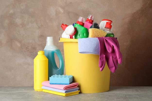 Flessen met wasmiddel en schoonmaakproducten op bruine achtergrond, ruimte voor tekst