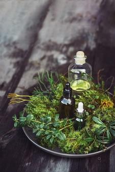 Flessen natuurlijke cosmetica serum, tincturen olie met verse planten op houten tafel