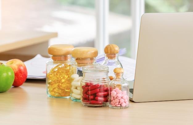 Flessen pillen, capsules en vitamines met notebookcomputer en vers fruit op het bureau van de voedingsdeskundige