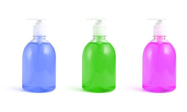 Flessen roze, groene en blauwe vloeibare zeep op een geïsoleerd wit
