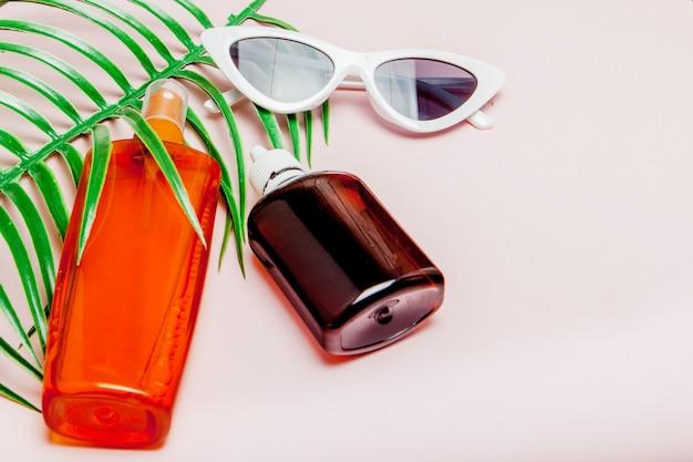 Flessen sunblock op heldere vierkante gele en roze achtergrond. het concept van het resort op zee, zomertijd. bovenaanzicht, plat lag, minimalisme, kopie ruimte