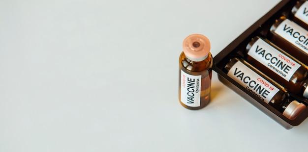 Flessen vaccin om de pandemie van het coronavirus te bestrijden. overwinning op sars-cov-2 / covid-19. ampullen met vaccin, doos op witte tafel met kopie ruimte.