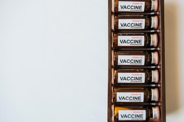 Flessen vaccin om de pandemie van het coronavirus te bestrijden. overwinning op sars-cov-2 / covid-19. sommige ampullen met vaccin in een doos op witte tafel met kopie ruimte.
