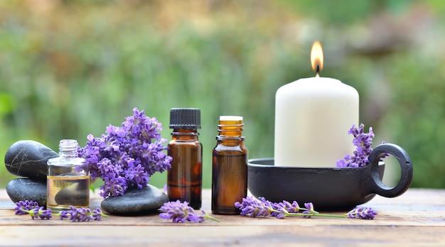 Flessen van etherische olie onder lavendel bloem gerangschikt op een houten tafel in de tuin met