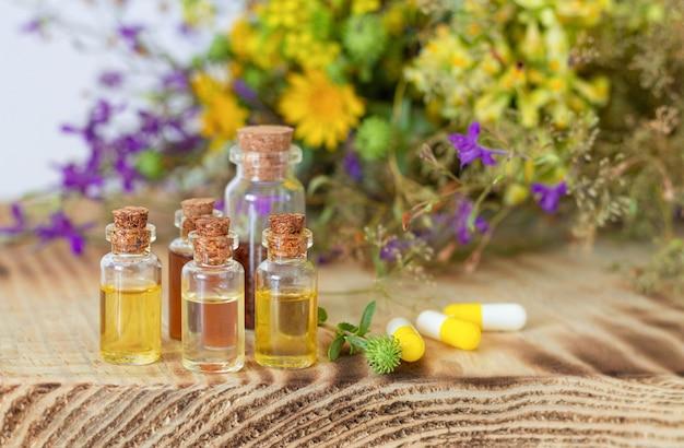 Flessen van natuurlijke etherische oliën naast kruidenpillen en verse helende bloemen