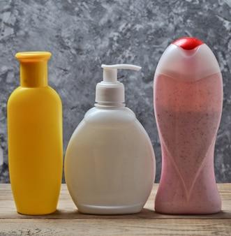 Flessen van producten voor een douche op een houten plank tegen een grijze betonnen muur. douchegel, shampoo, vloeibare zeep.