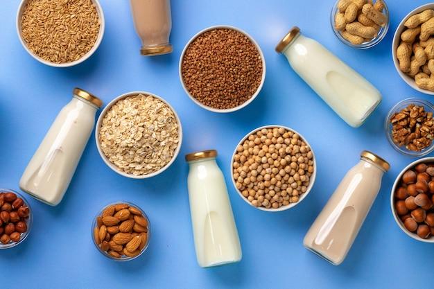 Flessen veganistische niet-zuivelmelk met verschillende noten op blauw