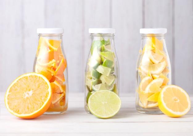 Flessen vers zomerwater met sinaasappelen met limoenen en citroenenplakken op houten met vers fruit