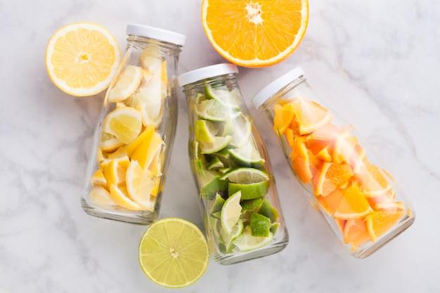 Flessen vers zomerwater met sinaasappels met limoenen en citroenenplakken op marmer met vers fruit