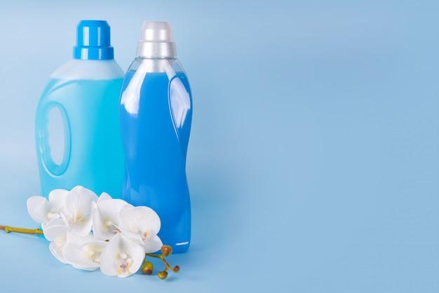 Flessen wasmiddel en wasverzachter met orchideebloemen op blauwe achtergrond