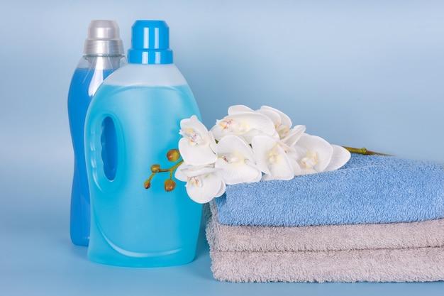 Flessen wasmiddel en wasverzachter met schone handdoeken en orchideebloemen op blauwe achtergrond