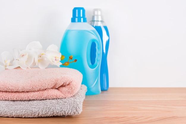 Flessen wasmiddel en wasverzachter met schone handdoeken en orchideebloemen op houten lijst