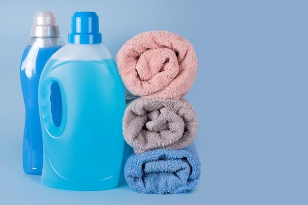 Flessen wasmiddel en wasverzachter met schone handdoeken op blauwe achtergrond