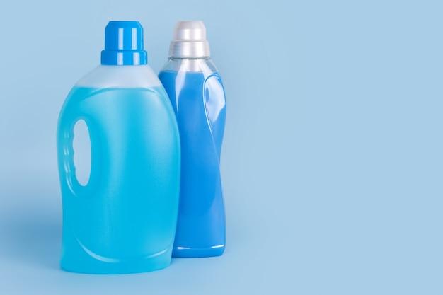 Flessen wasmiddel en wasverzachter op blauwe achtergrond