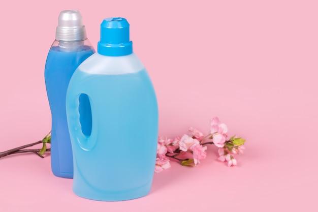 Flessen wasmiddel en wasverzachter op roze achtergrond met bloemen