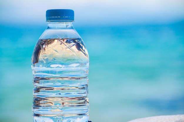 Flessen water op een warme dag op het strand.