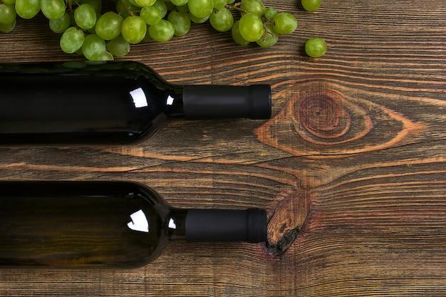Flessen wijn en rijpe druiven op houten achtergrond. bovenaanzicht. ruimte kopiëren. plat leggen. stilleven