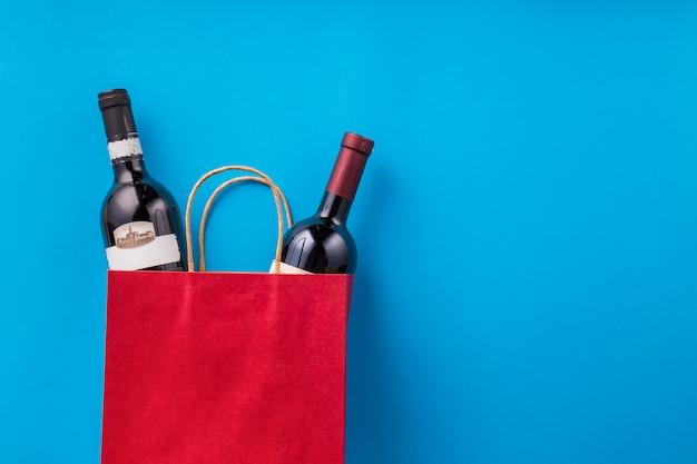 Flessen wijn in rode boodschappentas tegen blauw behang