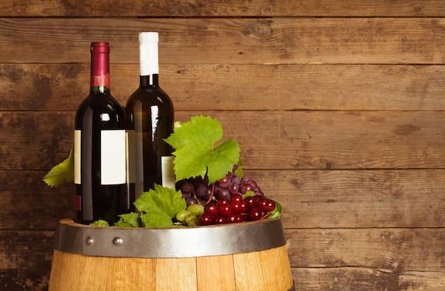 Flessen wijn op het eiken vat over oude armoedige houten achtergrond