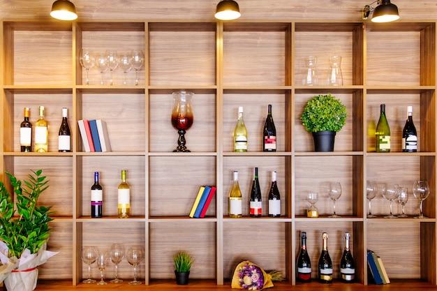 Flessen witte en rode wijn op een houten plank met boeken in privé wijnmakerij kast