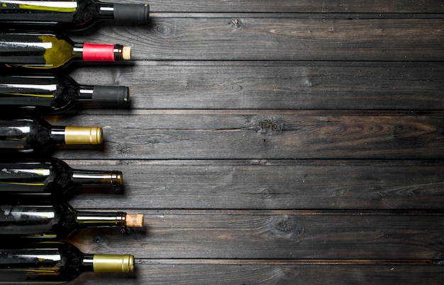 Flessen witte en rode wijn. op een houten tafel.