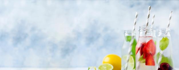 Flessenlimonade verfrissende zomerlimonade met limoen, aardbei, kers, komkommer en ijs op een grijze betonnen ondergrond