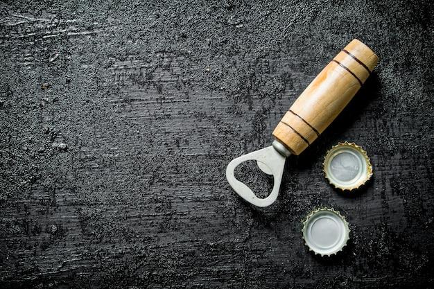 Flessenopener met bierhoezen. op zwarte rustieke achtergrond
