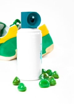 Flessenspray van het parfum van sportenmensen, tennisschoenen op witte achtergrond