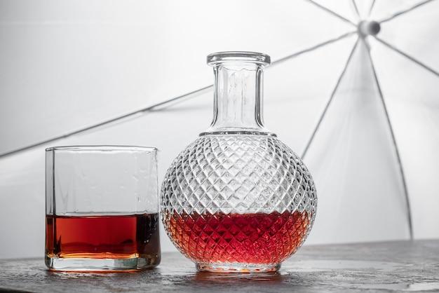 Flessenwhisky en glas wisky met ijs op zwarte achtergrond