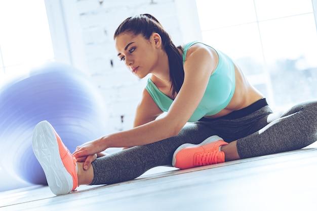 Flexibel blijven. mooie jongedame in sportkleding die zich uitstrekt terwijl ze op de vloer voor het raam in de sportschool zit