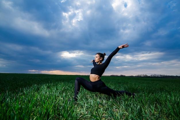 Flexibel meisje, acrobaat, gymnastiekbrug, handstand, sierlijke vrouw. in de natuur voert hij prachtige poses uit voor flexibiliteit, een sportmodel op een blauwe hemelachtergrond. Premium Foto