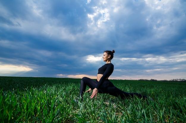 Flexibel meisje, acrobaat, gymnastiekbrug, handstand, sierlijke vrouw. in de natuur voert hij prachtige poses uit voor flexibiliteit, een sportmodel op een blauwe hemelachtergrond.
