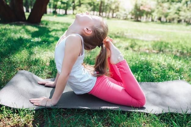 Flexibel meisje dat haar hoofd bereikt met het uiteinde van haar benen.