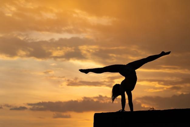 Flexibel meisje dat oefening op hemelachtergrond doet tijdens dramatische zonsondergang