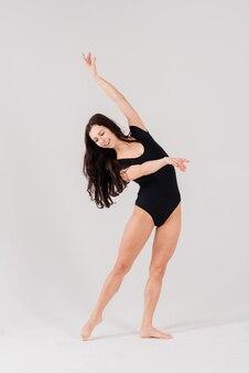 Flexibel wijfje in zwarte bodysuits, balletdanser, wit studioschot