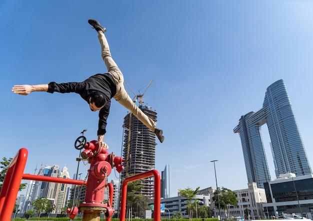 Flexibele acrobat houdt balans met één hand op de brandweerkraan met wazig dubai-stadsbeeld. concept van modern en veiligheid.