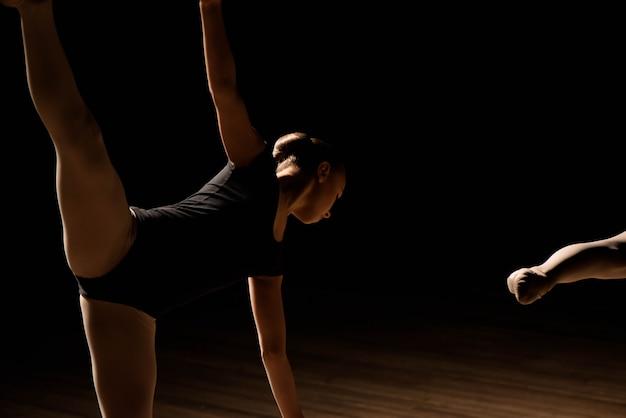 Flexibele ballerina's strekken zich uit over een donker verlichte scène